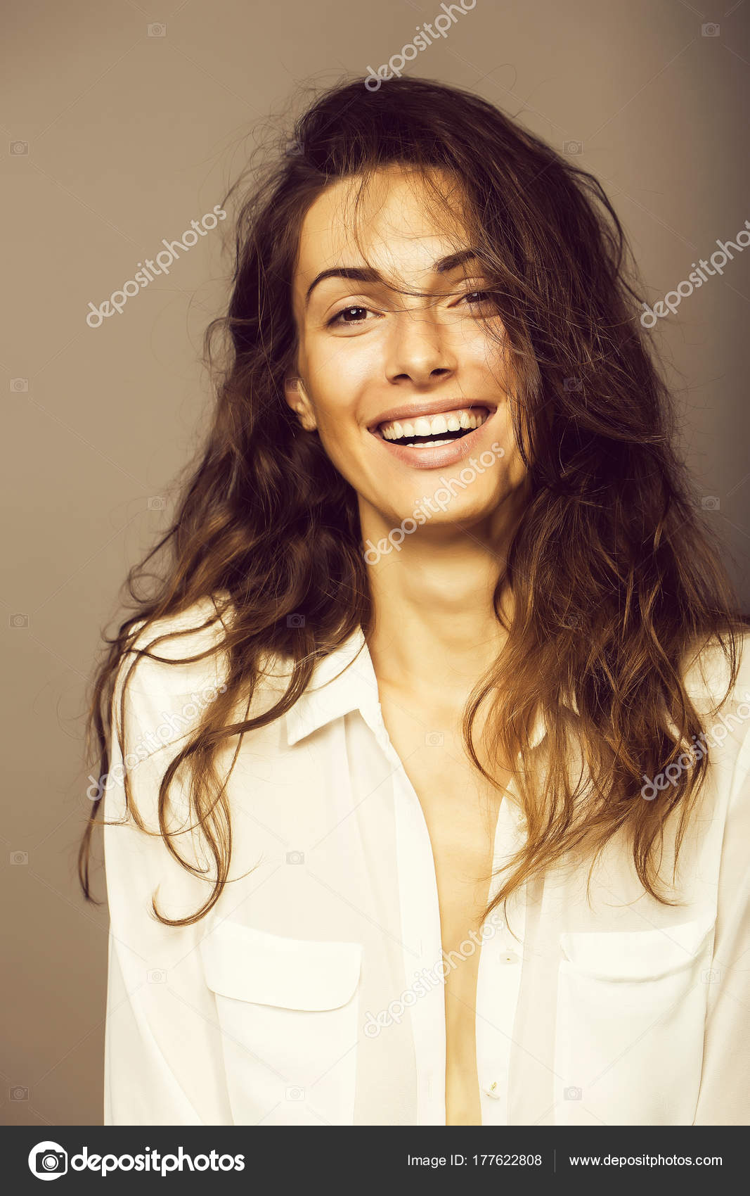 e460235265 Young sexy woman with pretty face and long brunette curly hair in white  shirt has slim body in studio on grey background — Photo by Tverdohlib.com