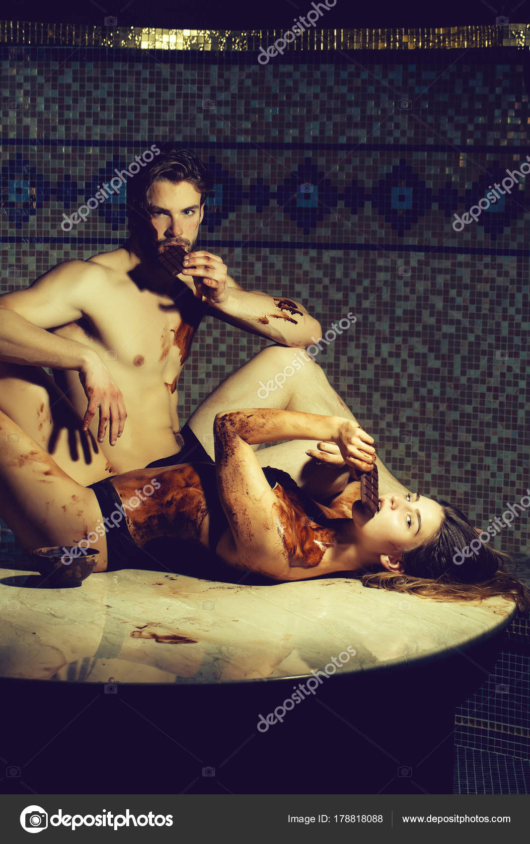 Pretty Woman Or Girl In Erotic Lingerie With Sexy Dirty Body And Handsome Bearded Man With Muscular Torso Eat Chocolate Bar After Massage In Beauty Spa