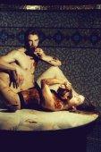 hübsche Frau oder Mädchen in erotischen Dessous mit sexy schmutzigen Körper und schöner bärtiger Mann mit muskulösem Oberkörper essen Schokoriegel nach der Massage im Beauty-Spa-Salon auf Mosaik Hintergrund in der Nähe Schüssel