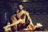 hübsche Frau oder Mädchen in erotischen Dessous mit sexy schmutzigen Körper und schönen aggressiven bärtigen mit muskulösen Oberkörper Essen Schokoriegel nach Massage im Spa Schönheitssalon auf Mosaik-Hintergrund in der Nähe von Schüssel