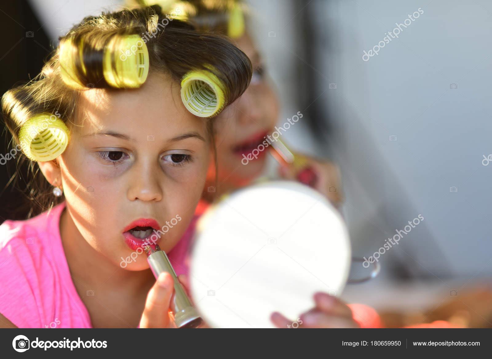 a3fb7cc343f Τα παιδιά με κραγιόν ματιά στον καθρέφτη. Έννοια της ομορφιάς και της  μόδας. Μικρά κορίτσια με σίδερα χαμόγελο και Παίξτε με αξεσουάρ μακιγιάζ  στην ...
