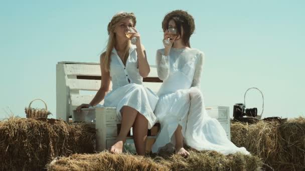 Lesben Paar. Freunde entspannen auf dem Bauernhof. Junge lesbische Paar spaßig auf einem Bauernhof
