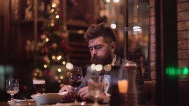Man in restaurant waiting a woman. Beautiful couple in a restaurant. Romantic couple dating in pub at night. Couple have romantic evening in restaurant.