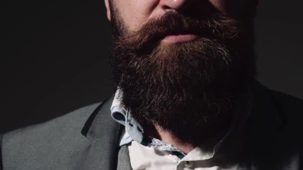 Csinos fiatal szakállas üzletember klasszikus öltöny alkalmazkodik a kabátja. Szakállas férfi, a különböző érzelmek.