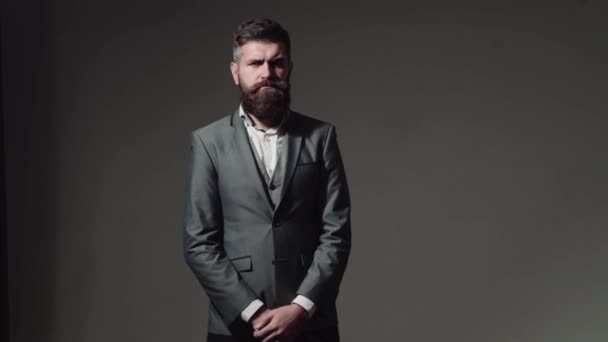 Handsome young bearded businessman in classic suit is adjusting his jacket . Bearded man with different emotions.