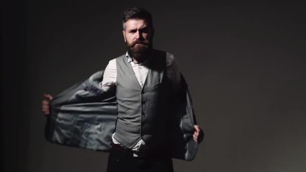 Pohledný mladý vousatý podnikatel v klasickém obleku upravuje jeho bundu. Vousatý muž s různými emocemi.