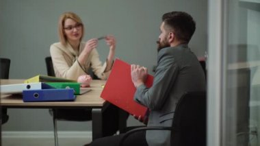 Office flirt - attractive woman flirting over desk with her coworker. Office play around. Job interview
