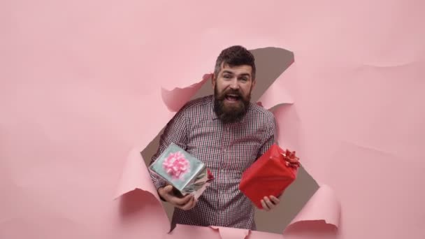 Vousatý muž s dárkovou krabičku. Vousatý muž s dárek. Muž s vousy na růžovém pozadí