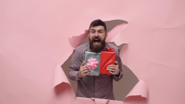 Vousatý muž s dárkovou krabičku. Vousatý muž s dárek. Muž s vousy na růžovém pozadí.