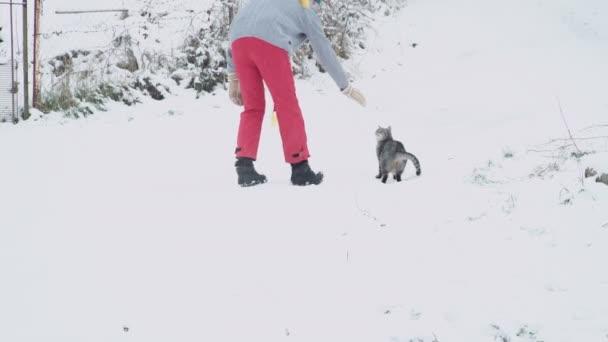 Wintertag. Mann mit Katze an einem verschneiten Wintertag