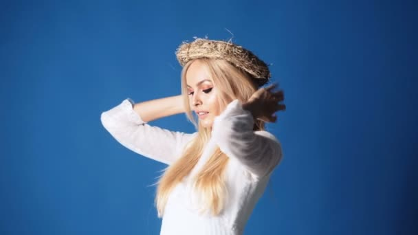 Blondýnka mladá žena v elegantní bílé šaty. Dívka pózuje na pozadí s kabelku. Dáma s jarní kytice květin. Módní. Ukrajinská dívka s květinami