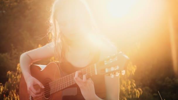 Dívka hraje na kytaru. Fragment. Žena hrát na kytaru na západ slunce.