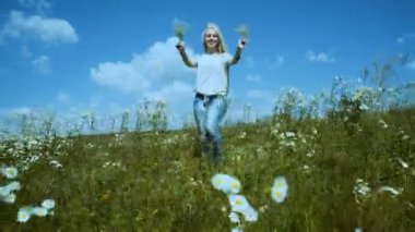 Chamomile flowers on a summer meadow. Beautiful woman in chamomile meadow.