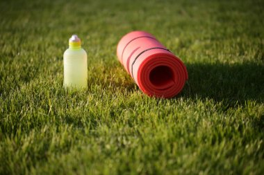 Water bottle and exercise mat in grass
