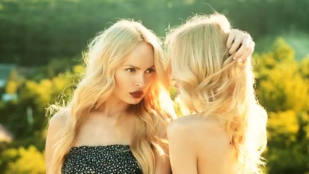 Two girls twins looking at each other. Beautiful two twins sisters together holding each other in hugs.