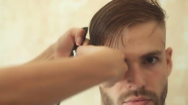 Fiatal férfi fodrászatban haj ellátás szolgáltatás fogalmát. Nagy idő a fodrászatban. Vidám fiatal szakállas férfi hajvágás, fodrász által egyre.