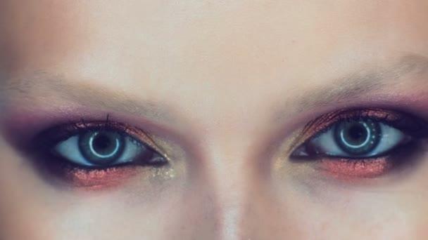 Maskérka aplikovat make-up na přitažlivou mladou ženou. Make-up pro mladé dívky. Mladá dívka v salonu krásy.