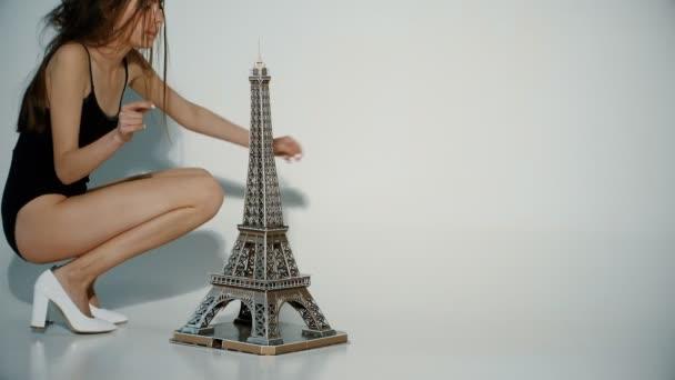 Eiffelova věž s krásnou holkou v Paříži. Elegantní pařížské mladá žena v černé košili a bílé boty sedí blízko: Eiffel tower na podlaze. Veselá dívka sní o Turistický výlet romantické Francie