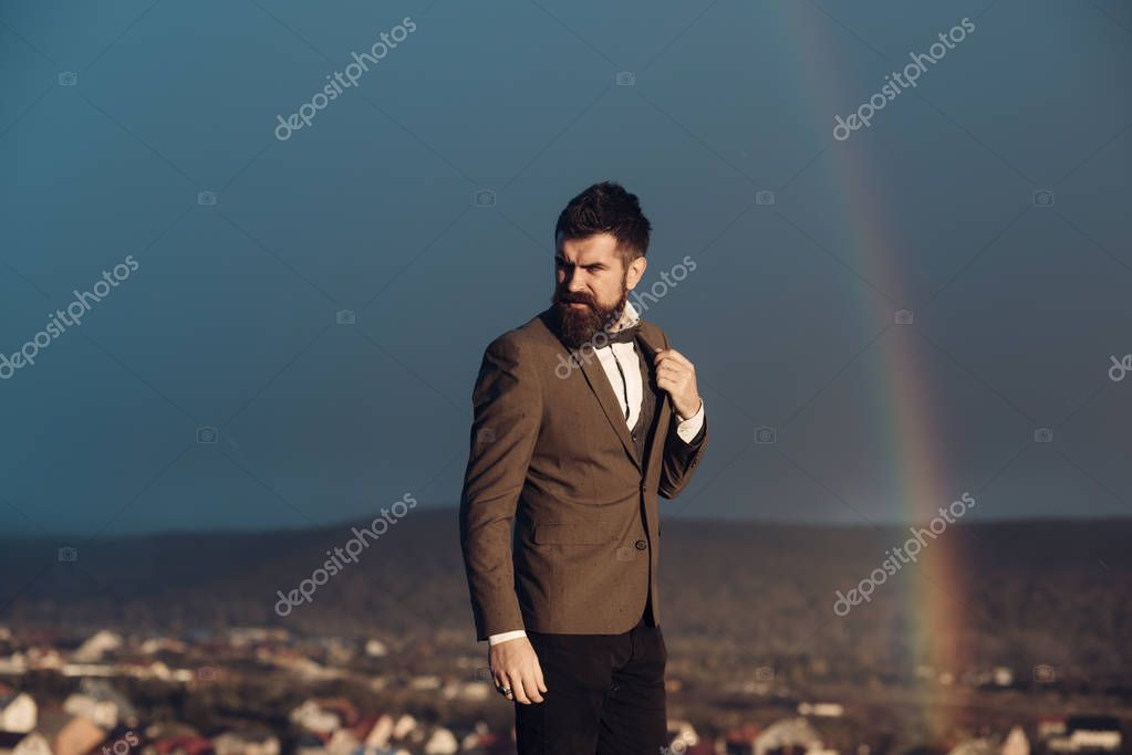 Man with beard and mustache and scenery with rainbow on background. Hipster with stylish appearance in front of dramatic sky with rainbow. Masculinity concept. Guy with strict face in classic suit.