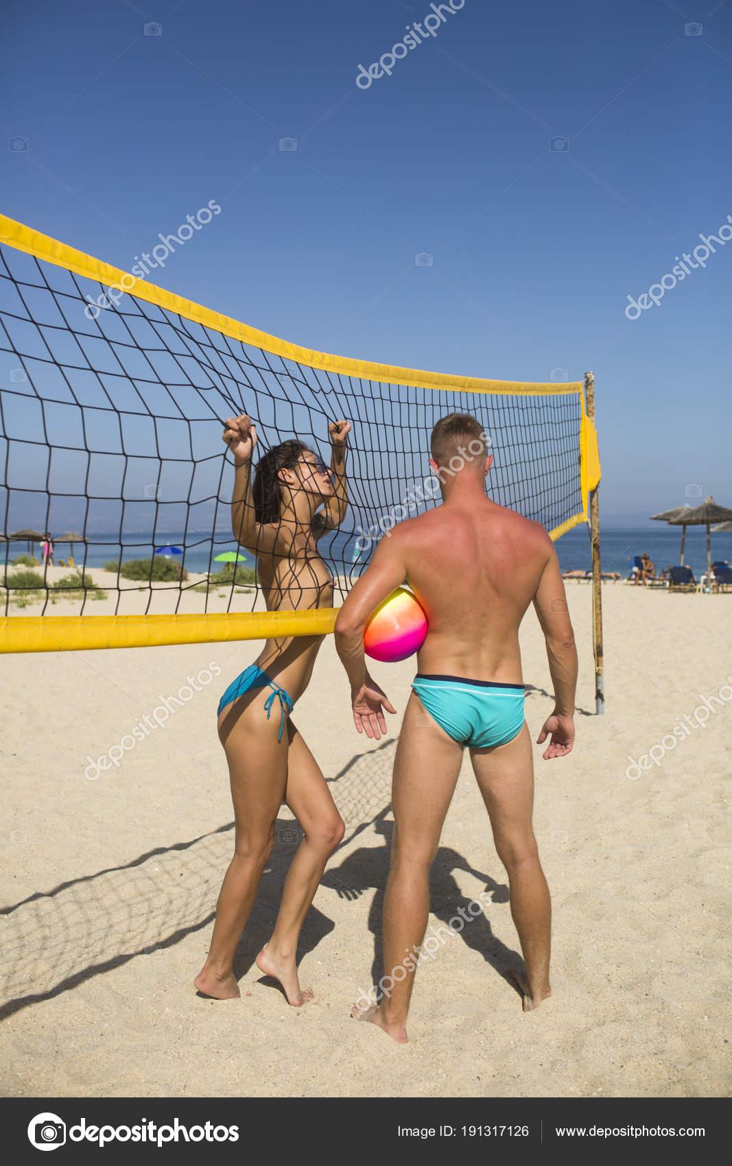 f36e6d7aa0380 Par divertirse jugando voleibol. Joven pareja activo deportivo parado cerca  de la red del voleibol