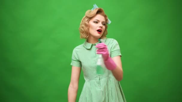 Kolík se žena v rukavice s úsměvem a utírání prachu pomocí spreje a prachovkou. Čisticí koncept s dodávkami. Krásná mladá žena je. Pin up čištění. Krásná žena v rukavice čištění