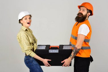 Repairman and girlfriend holding toolbox together, copy space. Smiling woman in helmet excited about renovation. Builders with toolbox, couple in love makes repair grey background. Renovation concept.