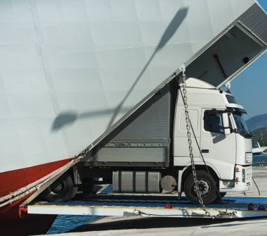 Camion rides out of ferry, ferryboat on sunny day. Intercontinental transport. ?argo van, truck, kamion transports goods or items between countries. International transportation concept.