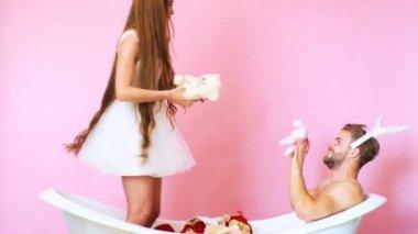 Toys. Bathtub. Luxury bathtub. Beautiful girl. Beautiful man. Beautiful woman playing in bathtub with toys. Young couple in bathtub