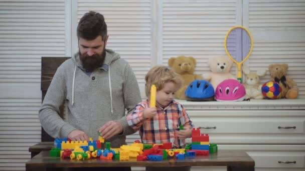 Otec a syn s úsměvem, vytvoření barevné konstrukce s kostek na hraní. Táta a dítě s hračkami sestavení z plastových bloků. Muž a chlapec hrát společně. Koncept rodina a dětství