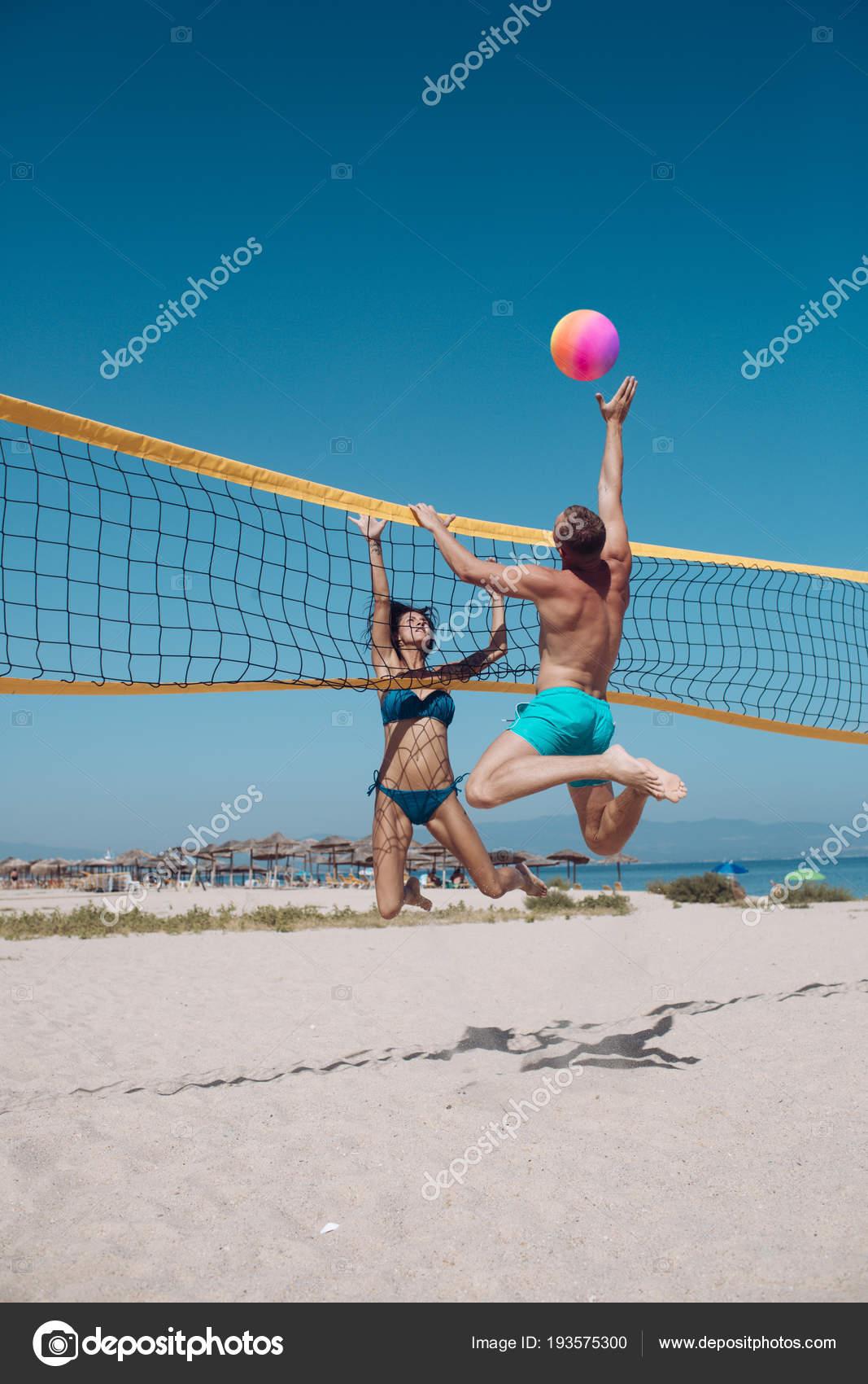 afee63be75245 Gente jugando al voleibol de playa divirtiéndose en el estilo de vida  activo deportivo. Hombre golpea voleibol juego en verano.