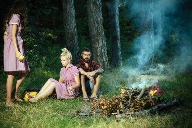 Kadın ve erkek, vintage tarzı kampında yangın. Arkadaşlar kamp ateşi sakin ol. Şenlik ateşi insanlara yeşil ormanda alev. Kamp, yürüyüş ve turistik. Yaz tatil kavramı.