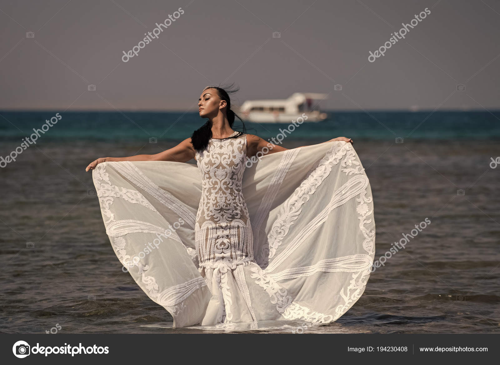 Mädchen-Braut posiert im Hochzeitskleid mit Schiff im Meer ...