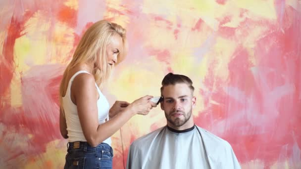 Male client getting haircut by hairdresser. Man at the hairdresser getting a haircut. Looks great. Pleasant handsome smiling man sitting in a barber shop while professional barber making a hair cut