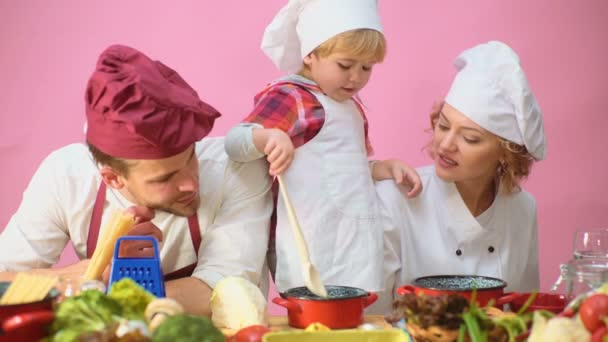 Cute little boy and his beautiful parents are smiling while cooking in  kitchen  Young family cooking food in kitchen  Happy family cooking  together  Happy young family with Mum, Dad child cooking