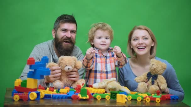 Young family play game with construction plastic blocks. Family games concept. Parents and kid with happy faces hold red bricks. Father, mother and son in playroom on light wooden background.