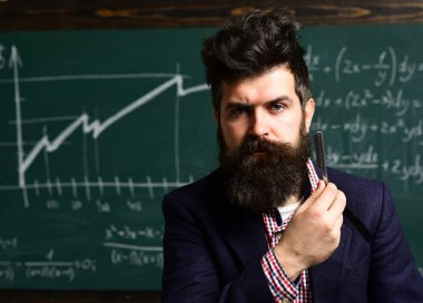 Student writing composition for annual exams preparation. Personal. business. Modern teacher hipster writing on big blackboard with math formula. Tutor or teacher must be an energetic person.