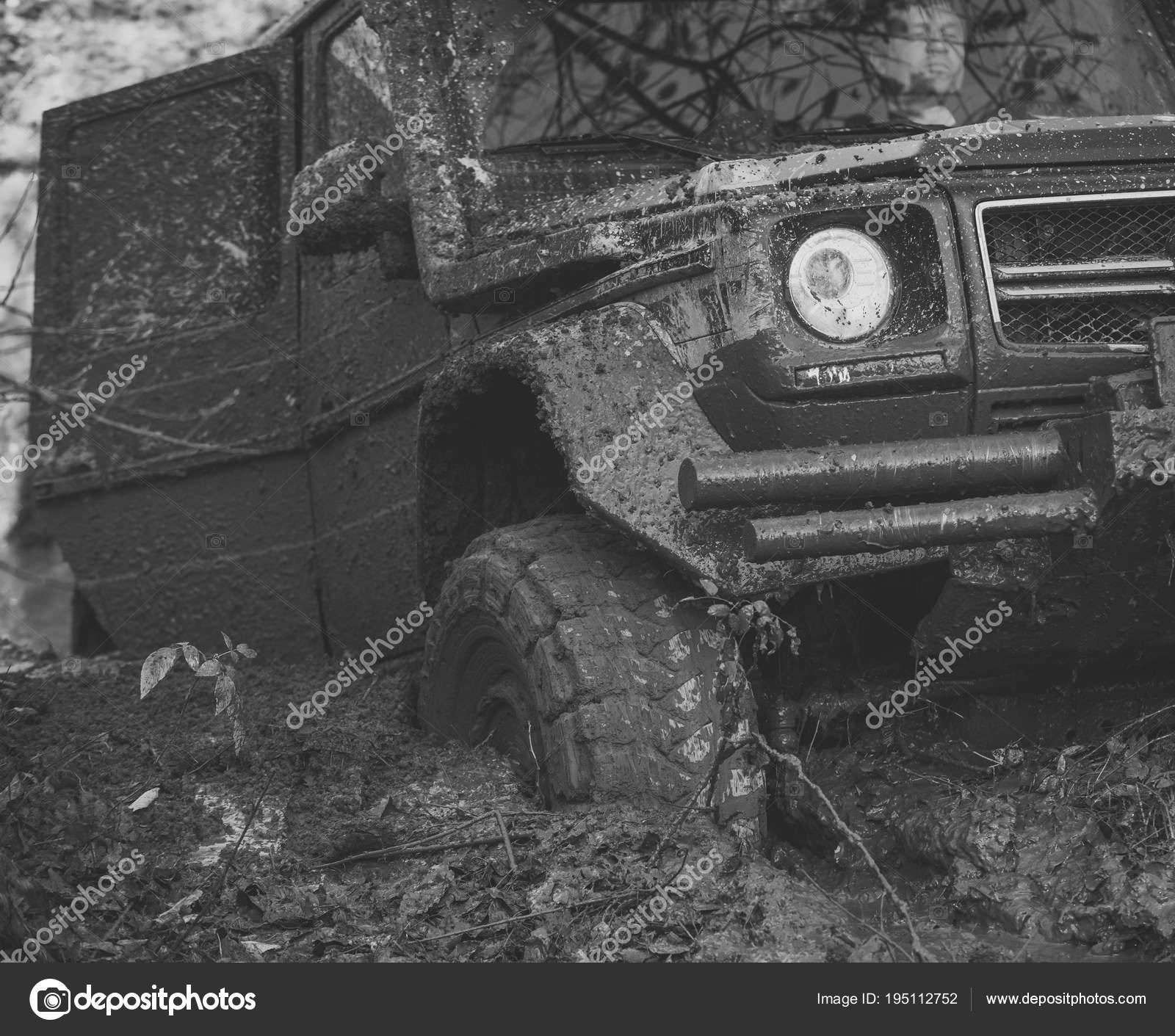 Dirty offroad car with open door stuck in deep rut  – Stock