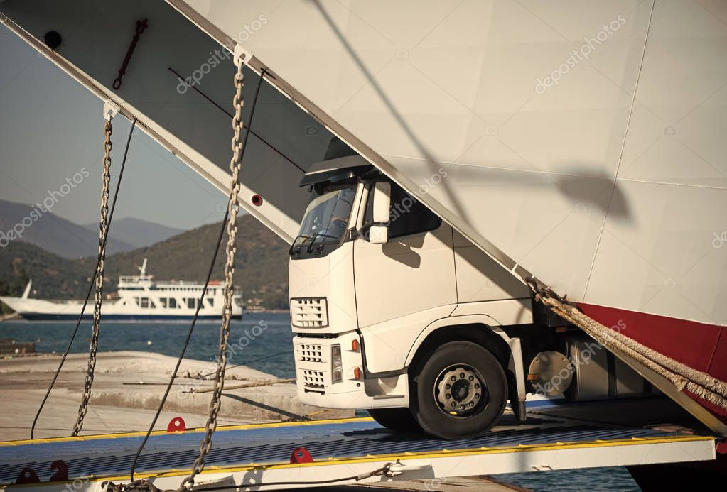 argo van, truck, kamion transports goods or items between countries. International transportation concept. Camion rides out of ferry, ferryboat on sunny day. Intercontinental transport.
