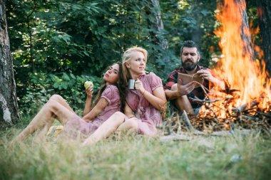 Ormanda kamp arkadaş grubu. Adam ateş tarafından kitap okumak. Güzel sarışın kız arkadaşı yeşil elma yerken kupa çay içme