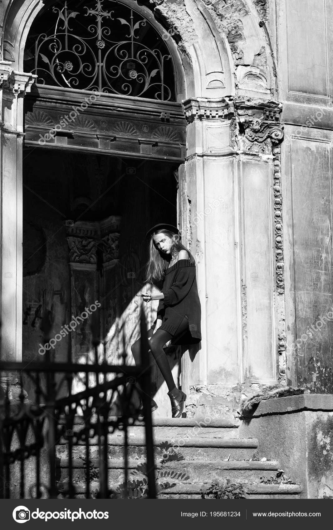 121c3fbc5f13f Moda joven mujer o chica con cara bonita con sombrero negro y vestido con  espejo y lápiz de labios rojo cerca de puerta de hierro de la vieja  arruinado ...