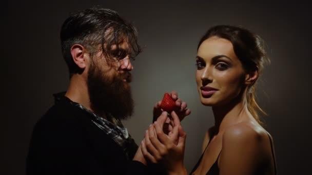 junges sexy Paar Frau mit hübschem Gesicht und brünetten Haaren mit nackten Schultern und schöner bärtiger Mann mit langem Bart, der rote Erdbeerfrüchte isst