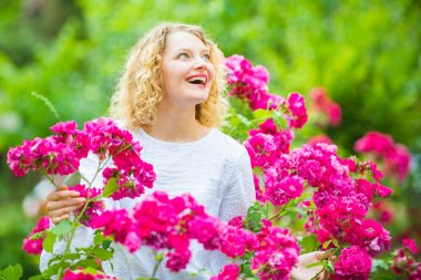 Beautiful woman with spring blooming rose flowers. Young smiling girl enjoys pink rose flowers. Summer time. Happy woman walking at rose garden. Pink rosebush blooming.