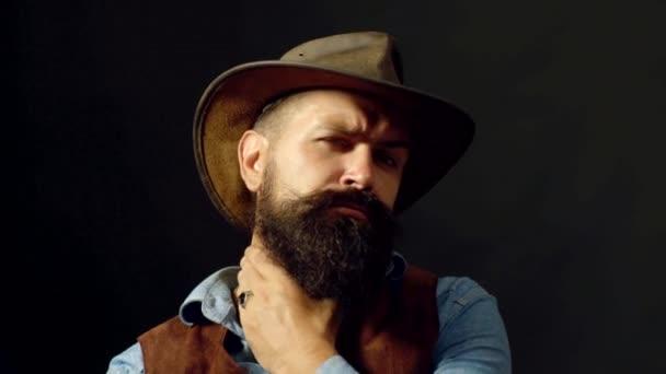 Drunk brutal man on black background. Confident handsome man. Portrait of stylish handsome bearded man with cowboy hat. Handsome man in style.