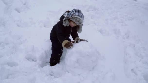 Děláme sněhuláka a zimní zábavu pro děti. Šťastné dítě si hraje se sněhulákem na zasněžené zimní procházce. Téma Vánoční svátky Zima Nový rok. Šťastný zimní čas.