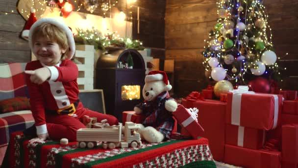 christmas kids - Glückskonzept. Kinder haben Spaß in der Nähe des Weihnachtsbaums drinnen. Neujahrskonzept. kleines Weihnachtsmann-Geschenk. glückliches Kind mit Weihnachtsmütze und Geschenk haben ein Weihnachtsfest.