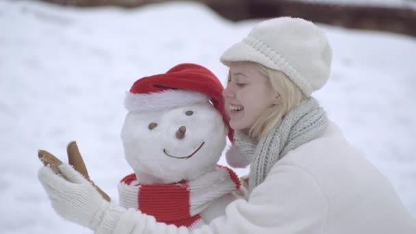 Boldog téli nő teszi hóember hóember egy havas téli séta. Téma karácsonyi ünnepek téli újév. Boldog téli időt!.