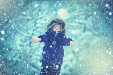 Winter landscape of forest and snow with cute child boy. Enjoying nature wintertime. Happy winter time. Well dressed enjoying the winter.