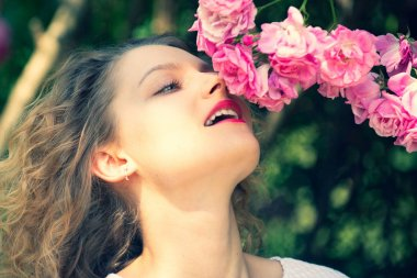 Close up portrait of tender woman with rose blossom. Summer time. Blossom around. Beautiful girl sniffes at rose bush. Relaxing and happiness concept. Flowers of pink rose.