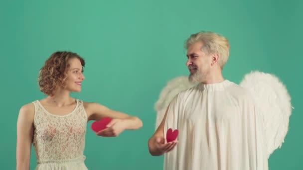 Skutečná historie Valentýna. Nejlepší Valentýnské nápady. Mladý pár na Valentýna - dávání srdce. Krásný pár se líbá. Den všech milenců. Izolováno na zelené.