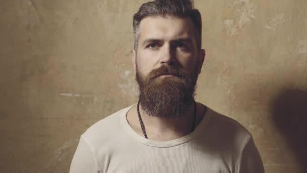 Pohledný vousatý muž se stylovými vousy a knírem na vážném obličeji v košili drží šálek nebo hrnek pije čaj nebo kávu ve studiu na vinobraní pozadí. Ranní drink.
